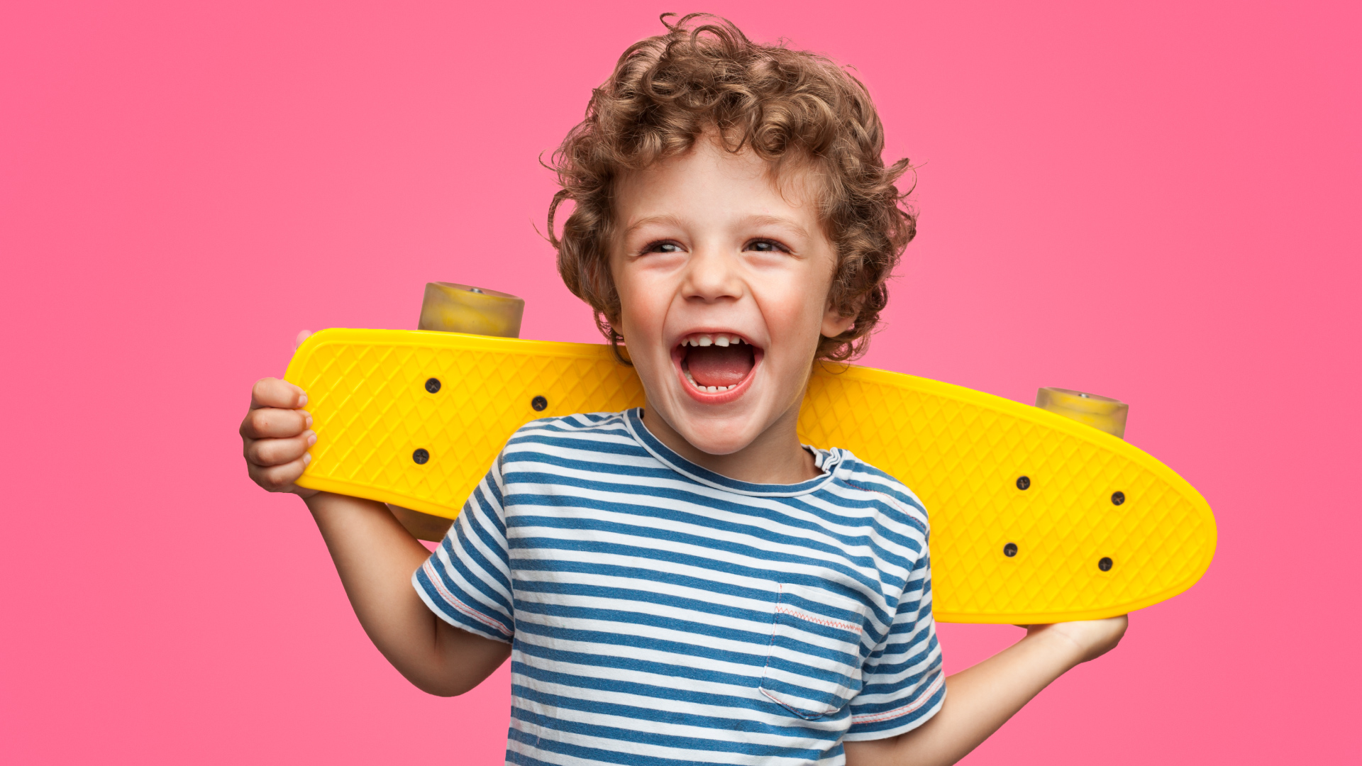 Smiling child holding a skateboard behind his back